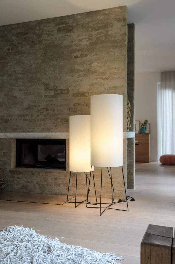 Floor lamp COLUMN standing in two sizes in front of a fireplace. The decorative design lamp on its cross foot exudes soft light trough its light grey fabric shade.